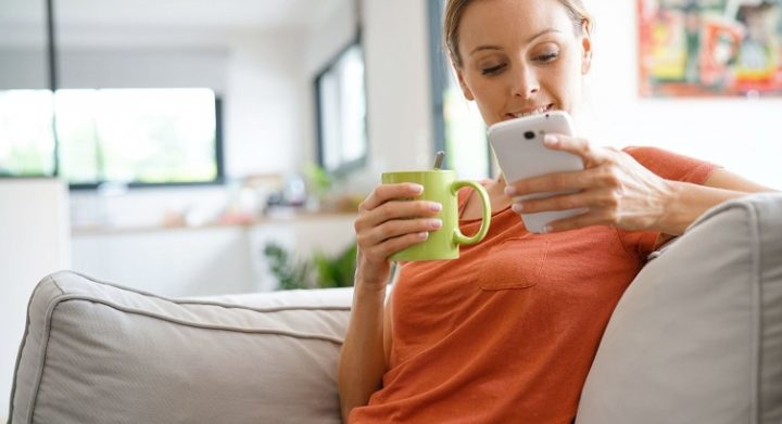 Woman relaxing in sofa connected with smartphone