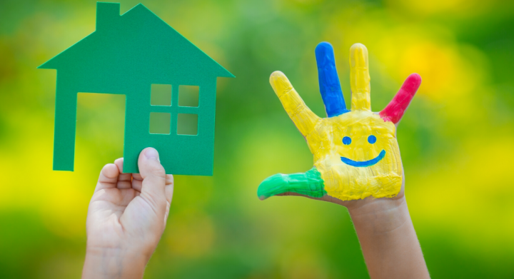 Photo of a child's hands holding cutout house