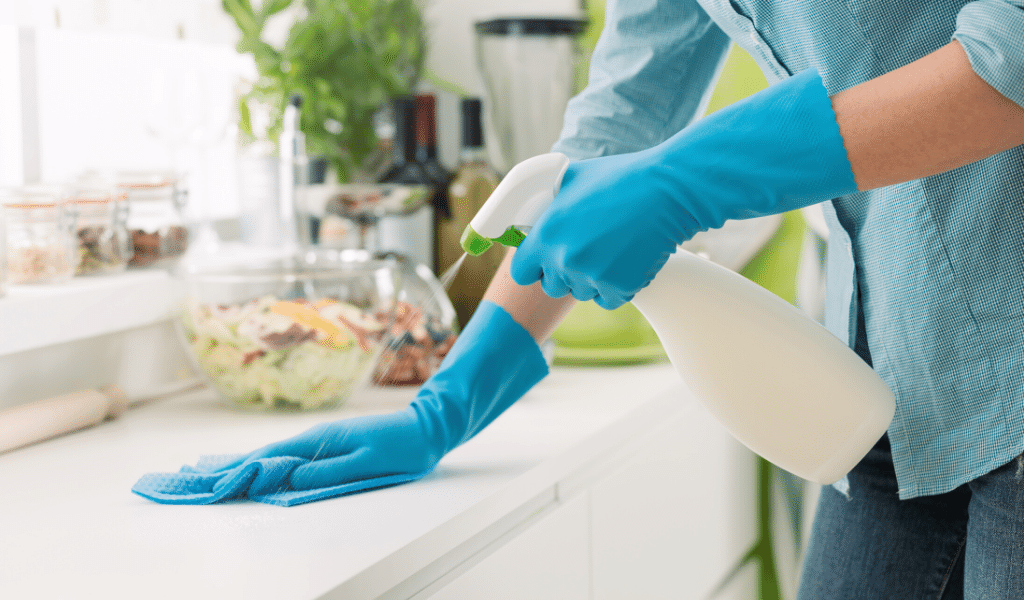woman cleaning surfaces with gloves
