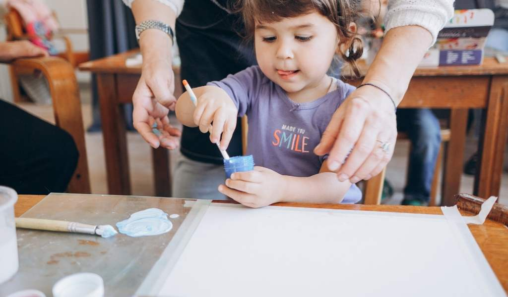 childminder helping a child paint