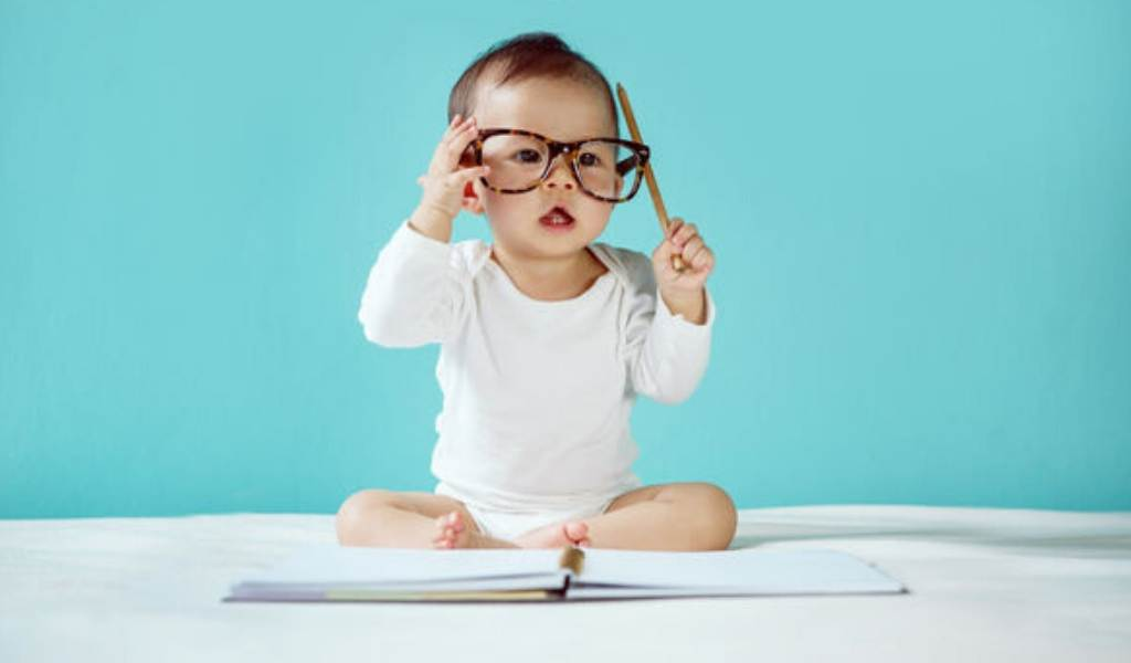 baby with glasses scratching head