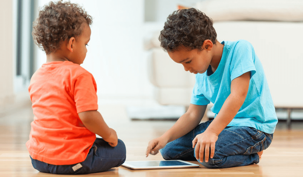 two boys playing with tablet on the floor