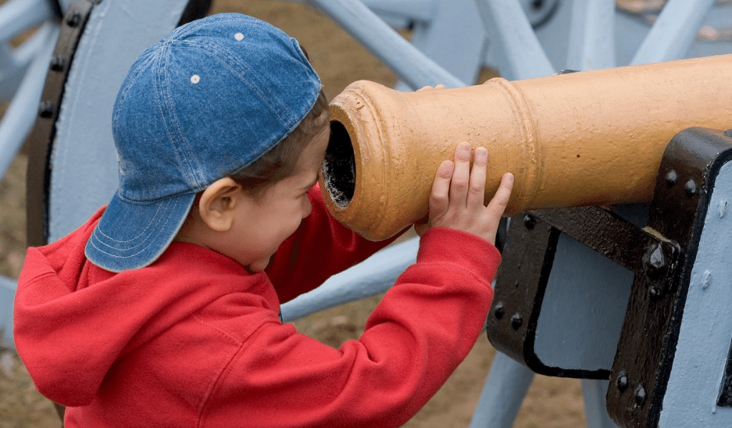 child curious looking through a cannon