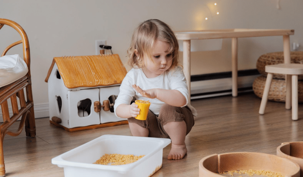 little girl playing with pasta and boxes