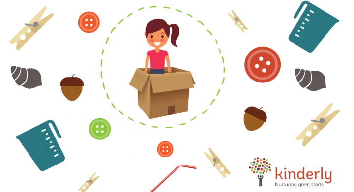 girl in a cardboard box surrounded by small objects