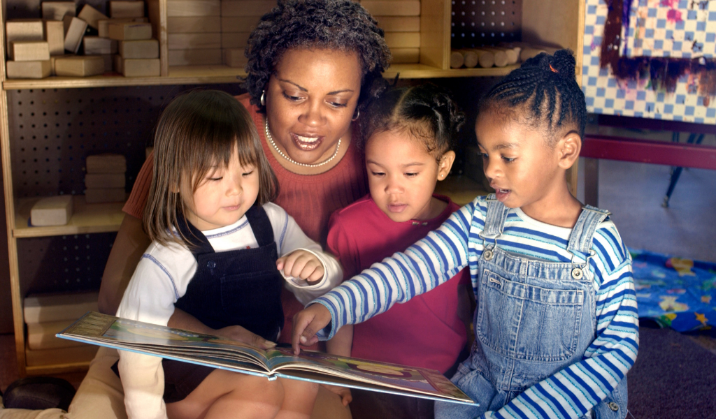 black childminder with children reading