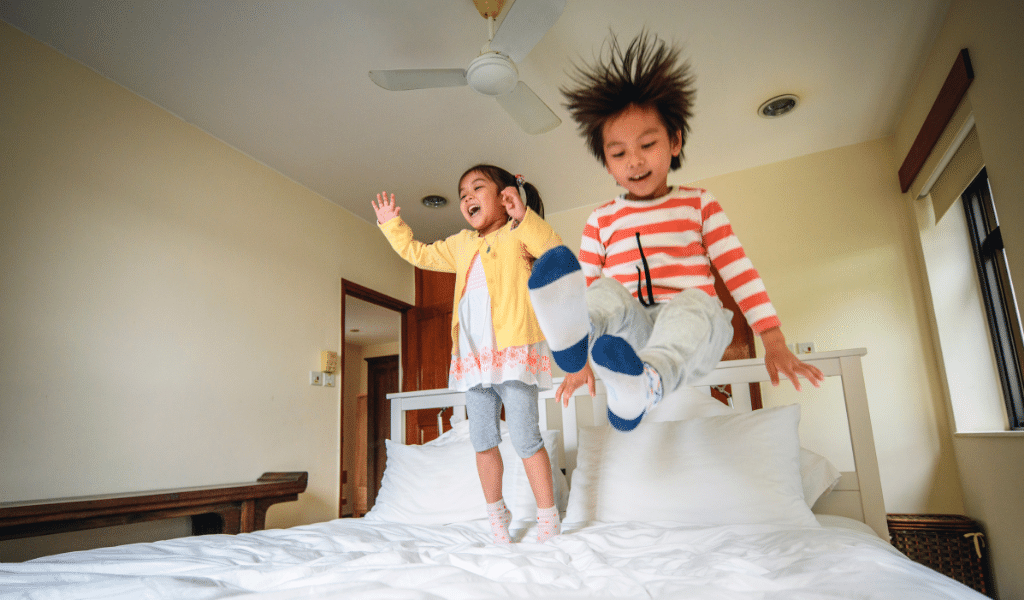 children jumping in bed