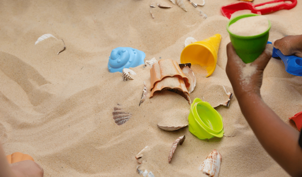 sand box full of shells and plastic toys