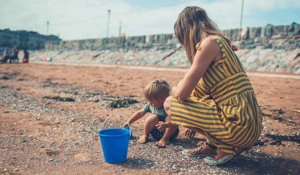 childminder playing with toddler on beach