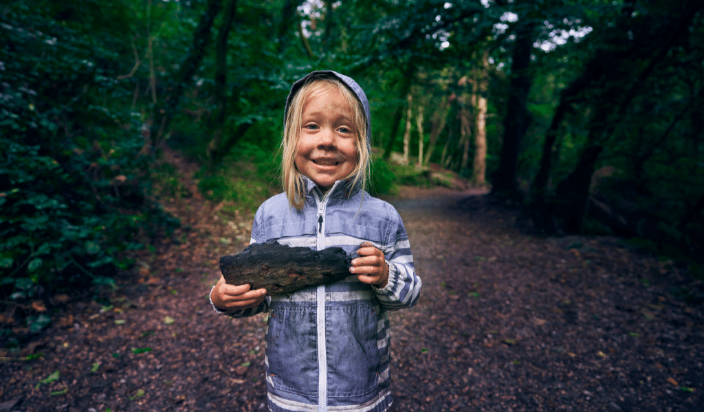 child holding a piece of wood in a forest