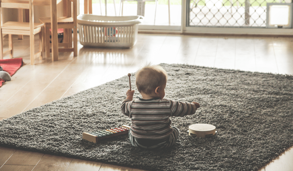 baby playing with instruments on floor